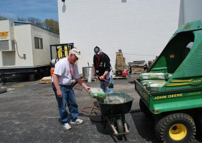 Jim L. & Bruce B. mixing mortar for a wall of Flint bricks being built in the Nostalgia Section of the Museum by two other club members.